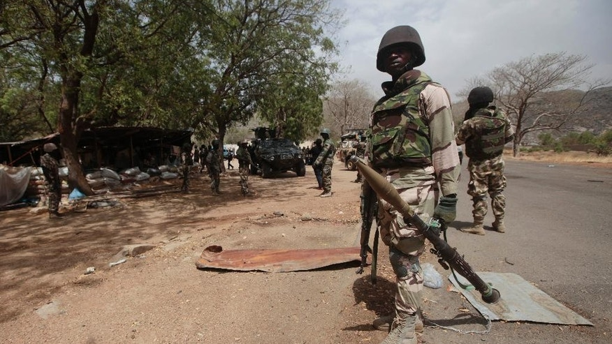 "In this photo taken Wednesday, April 8, 2015, Nigerian Soldiers man a check point in Gwoza, Nigeria, a town newly liberated from Boko Haram.   Each day brings new reports of atrocities, with mass graves being discovered in towns seized back from the militants who had set up a so-called ""Islamic caliphate"" across a great swath of northeast Nigeria. Boko Haram's nearly 6-year-old Islamic uprising in northeast Nigeria that has killed thousands — a reported 10,000 just last year — and forced more than 1.5 million from their homes. (AP Photo/Lekan Oyekanmi)"