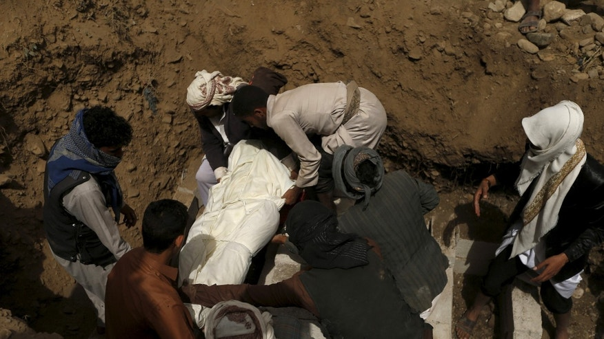April 10, 2015 - People mourn a victim of a Saudi-led air strike at a grave in Sanaa, Yemen. Saudi-led coalition air strikes hit Yemen for a 16th straight day. A car bomb exploded near a security building used by rebel Houthi fighters in central Yemen Friday, leaving at least 7 dead.