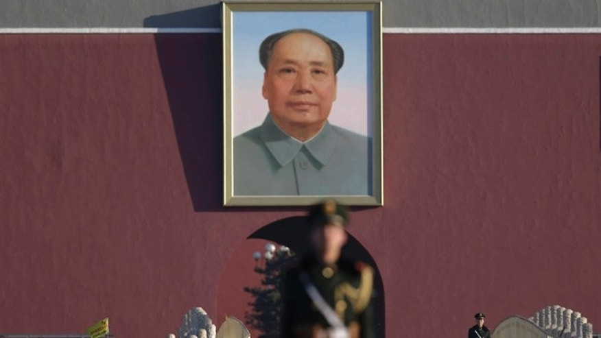 FILE - In this March 10, 2015 file photo, Chinese paramilitary policemen stand watch near a portrait of Mao Zedong after they sealed off Tiananmen Square to the public during a plenary session of the Chinese People's Political Consultative Conference at the Great Hall of the People in Beijing. (AP Photo/Andy Wong, File)