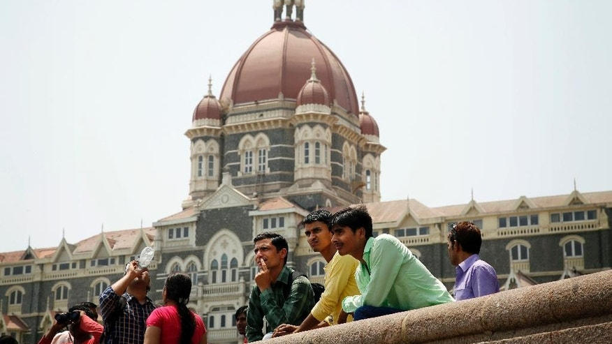 Indians stand outside the Taj Mahal hotel, which was one of the sites of the Mumbai terror attack, in Mumbai, India, Friday, April 10, 2015. A Pakistani court on Thursday, April 9, 2015, ordered the release of the main suspect Zaki-ur-Rehman Lakhvi in the 2008 Mumbai attacks for the second time in less than a month, a defense lawyer said. (AP Photo/Rajanish Kakade)