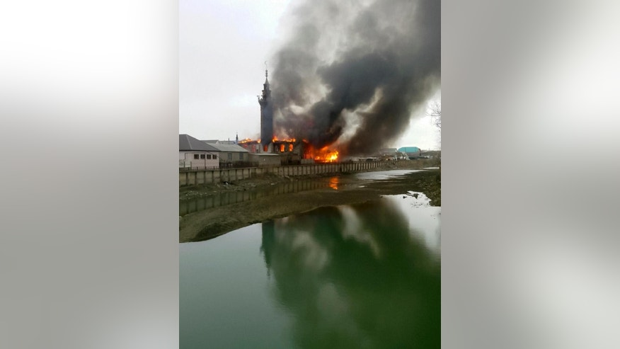 Black smoke and fire rising over the main mosque in Kizlyar, a town in the southern Russian republic of Dagestan, Friday, April 10, 2015. Police spokeswoman Fatina Ubaidatova says no one was hurt when the fire swept through the mosque in the city of Kizlyar, located near the border with Chechnya. (AP Photo/NewsTeam, Zaur Khalikov)