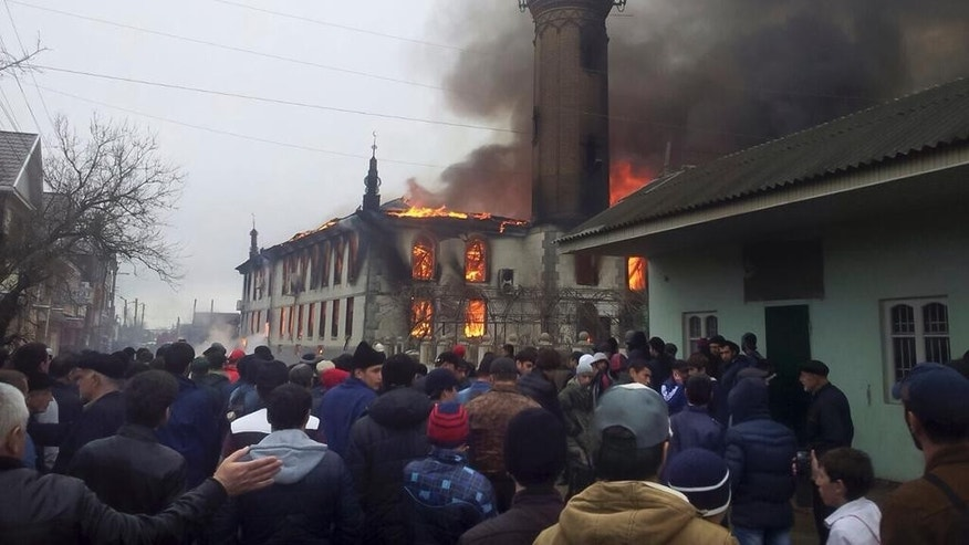 People watch as black smoke and fire rising over the main mosque in Kizlyar, a town in the southern Russian republic of Dagestan, Friday, April 10, 2015. Police spokeswoman Fatina Ubaidatova says no one was hurt when the fire swept through the mosque in the city of Kizlyar, located near the border with Chechnya. (AP Photo/NewsTeam, Zaur Khalikov)