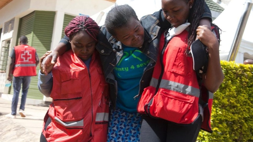 FILE- In this file photo of Monday, April 6, 2015, Red Cross staff help a grieving relative at the Chiromo Funeral Parlour. A small army of counselors, many wearing Kenya Red Cross vests are deployed at the Chiromo Funeral Parlour to lend support to relatives of some of the 148 people killed in the April 2 attack on Garissa University College in eastern Kenya, by the extremist group al-Shabab.(AP Photo/Sayyid Azim,  FILE)
