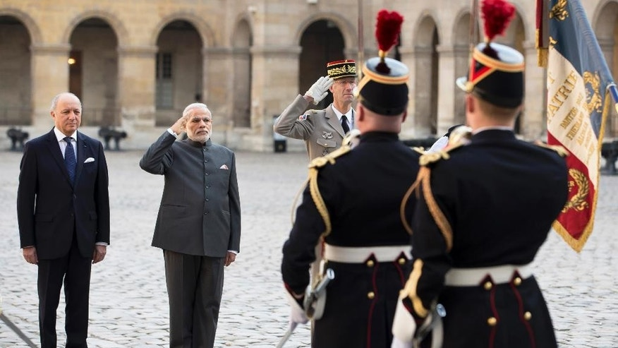 French foreign minister Laurent Fabius, left, and Indian prime minister Narendra Modi, second right, salute the French flag during a welcoming ceremony in the courtyard of the Hotel des Invalides in Paris, France, Friday April 10, 2015.  Indian Prime Minister Narendra Modi has arrived in France as part of a European tour. French authorities are hoping to build up already-strong contacts with the fast-growing Asian nation amid talks about a possible big fighter-jet deal. (AP Photo/Ian Langsdon/pool)