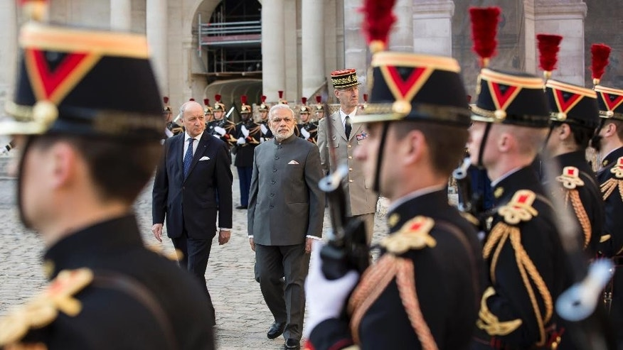 French foreign minister Laurent Fabius, center left, and Indian prime minister Narendra Modi, center right, review an honor guard during a welcoming ceremony in the courtyard of the Hotel des Invalides in Paris, France, Friday April 10, 2015.  Indian Prime Minister Narendra Modi has arrived in France as part of a European tour. French authorities are hoping to build up already-strong contacts with the fast-growing Asian nation amid talks about a possible big fighter-jet deal. (AP Photo/Ian Langsdon/pool)