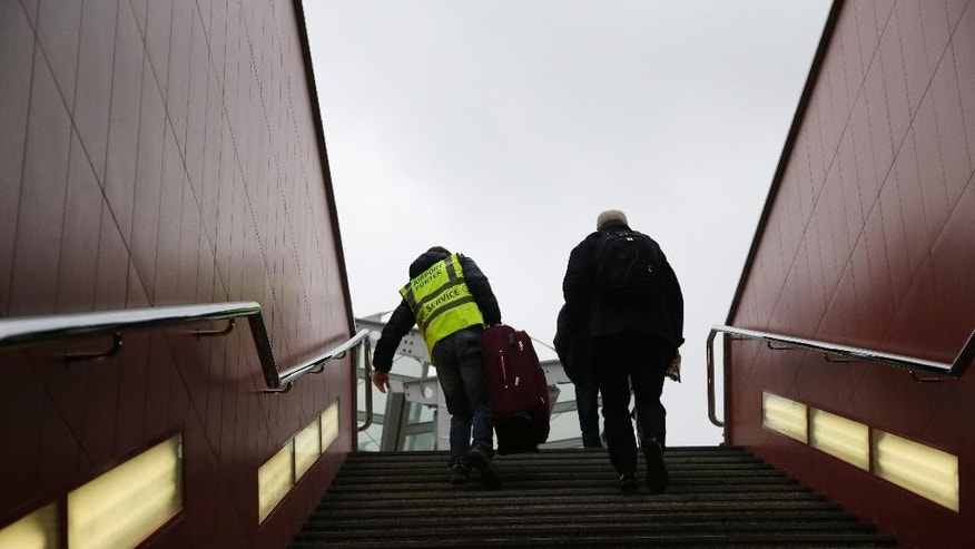 In this picture taken on Wednesday, April 8, 2015, a porter helps to carry a luggage to traveler on their way to the airport in Prague, Czech Republic. On the way to the Vaclav Havel Airport people using a bus have to climb 32 steps of a steep staircase from the subway station to the bus terminal. (AP Photo/Petr David Josek)