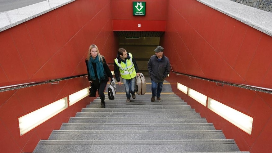 In this picture taken on Wednesday, April 8, 2015, a porter helps to carry a luggage to travelers on their way to the airport in Prague, Czech Republic. On the way to the Vaclav Havel Airport people using a bus have to climb 32 steps of a steep staircase from the subway station to the bus terminal. (AP Photo/Petr David Josek)
