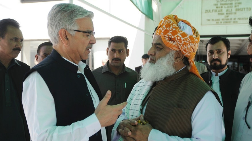 April 10, 2015 - Pakistan's Defense Minister Khawaja Muhammad Asif, left, talks with Maulana  Fazalur Rehman, chief of religious party Jamat Ulema-e-Islam outside the  Parliament after attending a joint session to discuss the crisis in Yemen, in Islamabad, Pakistan. Pakistan's parliament decided not to join the Saudi-led coalition targeting Shiite rebels in Yemen.
