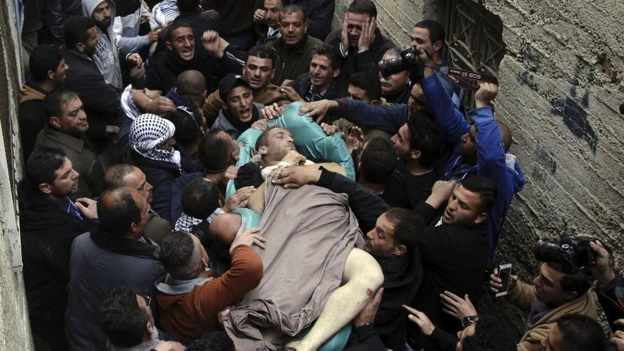 Mourners carry the body of Ziyad Awad during his funeral in Beit Ummar, West Bank, Friday, April 10, 2015. Awad was killed in clashes with Israeli soldiers, following the funeral of his cousin who died three months after being released from an Israeli jail. (AP Photo/Mahmoud Illean)