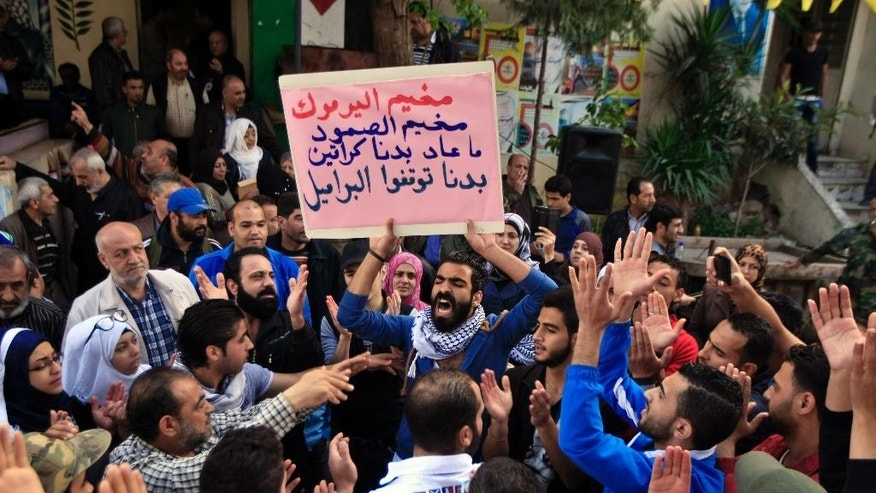 "Palestinian refugees, including some who fled from Yarmouk camp in Damascus, chant slogans as they hold an Arabic placard that reads ""Yarmouk camp, steadfast camp, we do not want aid, we need you to stop the barrel bombs,"" to show their solidarity with thousands of besieged Palestinians in Yarmouk which was overrun by Islamic State militants last week, during a demonstration in the Ein el-Hilweh camp near the southern city of Sidon, Lebanon, Lebanon, Friday, April 10, 2015. The Palestine Liberation Organization says it won't be drawn into military action against the Islamic State group in Yarmouk. (AP Photo/Mohammed Zaatari)"