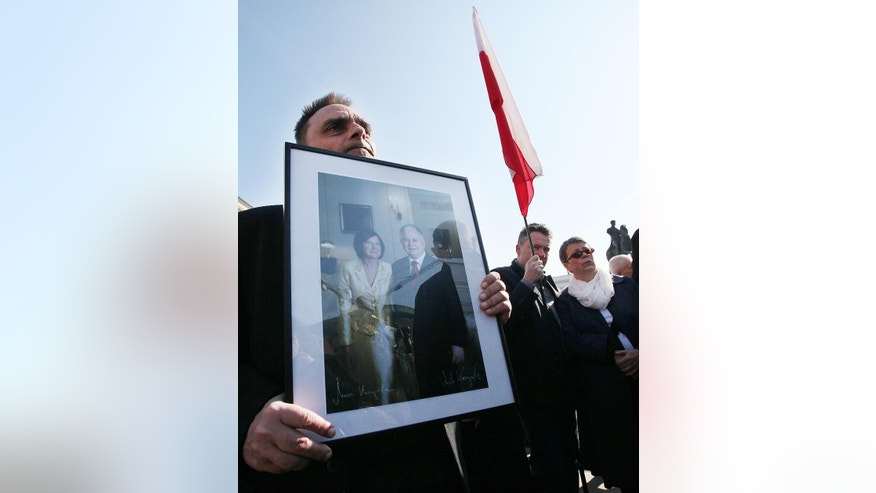 People hold a flag and a photo of of late President Lech Kaczynski and his wife Maria in front of the Presidential Palace during a ceremony marking the 5th anniversary of the presidential plane crash near Smolensk, Russia, Friday, April 10, 2015, in Warsaw, Poland. (AP Photo/Czarek Sokolowski)