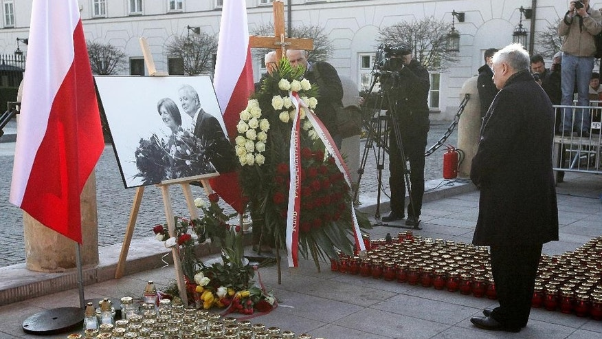 Jaroslaw Kaczynski, Law and Justice party leader and twin brother of late Polish president Lech Kaczynski, prays at the Presidential Palace during a ceremony marking the 5th anniversary of the presidential plane crash near Smolensk, Russia, Friday, April 10, 2015, in Warsaw, Poland. The photograph at left shows Lech Kaczynski and his wife Maria, who also died in the crash. (AP Photo/Czarek Sokolowski)