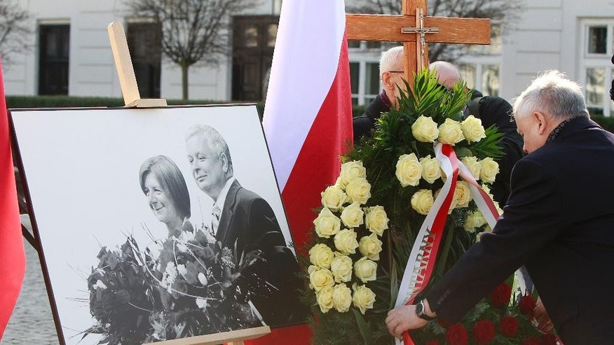 Jaroslaw Kaczynski, Law and Justice party leader and twin brother of late Polish president Lech Kaczynski, lays a wreath at the Presidential Palace during a ceremony marking the 5th anniversary of the presidential plane crash near Smolensk, Russia, Friday, April 10, 2015, in Warsaw, Poland. The photograph at left shows Lech Kaczynski and his wife Maria, who also died in the crash. (AP Photo/Czarek Sokolowski)