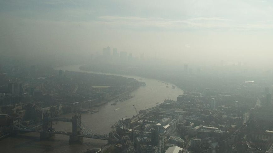 In this general view of London, taken through glass, showing Tower Bridge, lower left, over the river Thames and looking east towards Canary Wharf, top, which is just visible through the haze and smog in London, Friday, April 10, 2015. Southern Britain and northern France are suffering high levels of air pollution due to stagnant air, though an atlantic weather system will bring fresher conditions Saturday. (AP Photo/Alastair Grant)