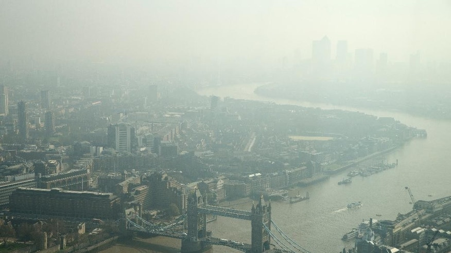 In this general view of London, taken through glass, showing Tower Bridge and looking east towards Canary Wharf, top right, which is just visible through the haze and smog in London, Friday, April 10, 2015. Southern Britain and northern France are suffering high levels of air pollution due to stagnant air, though an Atlantic weather system will bring fresher conditions Saturday, according to weather forecast predictions. (AP Photo/Alastair Grant)