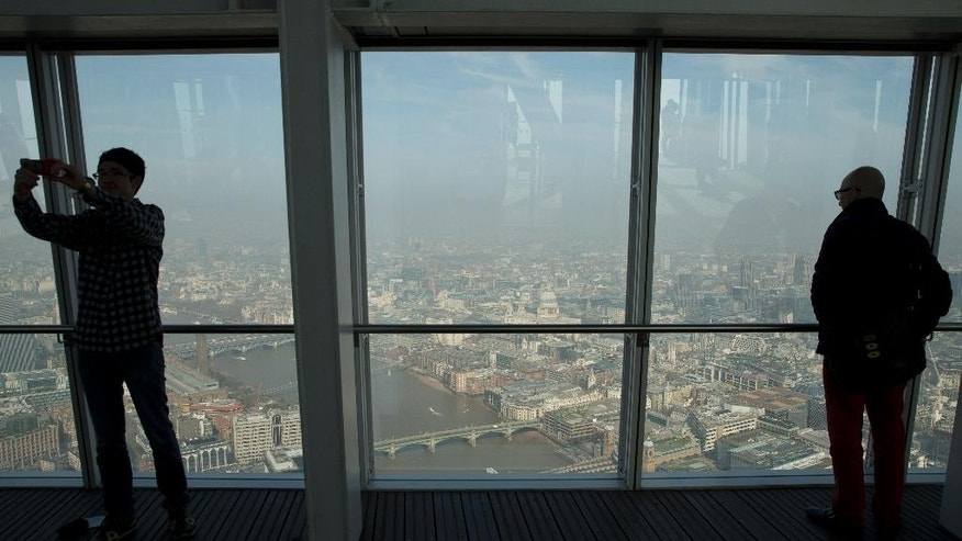 Visitors to the Shard building viewing platform take photos of the City of London, with St Paul's Cathedral, seen at centre, with a layer of smog and haze visible above the city, in London, Friday, April 10, 2015. Southern Britain and northern France are suffering high levels of air pollution due to stagnant air, though an atlantic weather system will bring fresher conditions Saturday. (AP Photo/Alastair Grant)