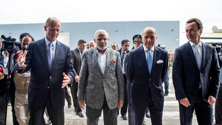 Tom Enders, Airbus Group CEO, left, and Fabrice Bregier, Airbus CEO, right, welcome India Prime Minister Narenda Modi, and French Foreign Minister Laurent Fabius, second right, as they visit the Airbus A380 Final Assembly Lane, in Blagnac, Southern France, Saturday April 11, 2015. (AP Photo/Fred Lancelot, Pool)