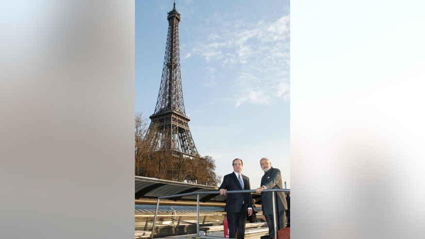 Indian Prime Minister Narendra Modi, right,  and French President Francois Hollande enjoy a tour on the Seine Rive, past the Eiffel Tower, on a pleasure boat in Paris, France.  Friday April 10, 2015.  India will purchase 36 of Dassault Aviation's French-manufactured Rafale fighter jets, Prime Minister Narendra Modi said on Friday during his visit to Paris. (AP Photo/Benoit Tessier, Pool)