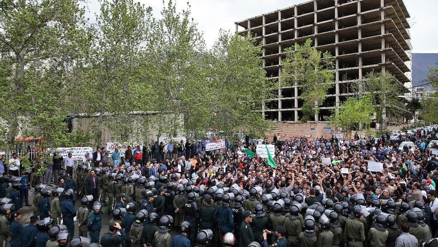 "A group of Iranian protesters chant slogans in front of the Saudi Embassy, while police officers deploy to protect the embassy, in Tehran, Iran, Saturday, April 11, 2015. Defying a government ban, hundreds of Iranians protested after two male Iranian pilgrims alleged abuse after Saudi officers at Jeddah's international airport searched them. Demonstrators shouted: ""Shame on you!"" and ""Death to House of Saud!"" in reference to the ruling family.  (AP Photo/Ebrahim Noroozi)"