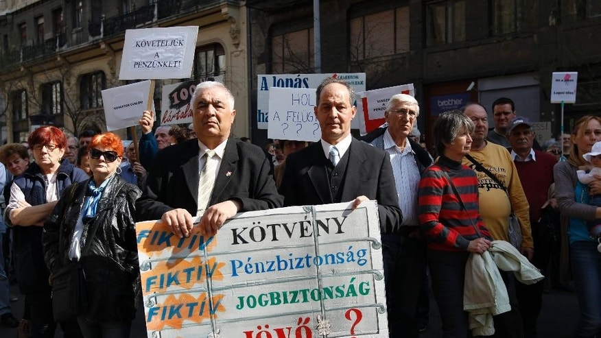 "Holding placards, investors affected by the bankruptcy of Quaestor Group, a Hungarian private company, protest against an apparent fraud of the firm and demand total compensation of their losses in front of an office of the company in downtown Budapest, Hungary, Saturday, April 11, 2015.  Some 400 investors protested outside an office of the Quaestor brokerage, supervised since last month by the National Bank of Hungary after being suspected of issuing some 150 billion forints (505 million euros, US $535 million) in unauthorized bonds.  The inscription of the placard at center reads ""Fictitious bond - Fictitious bond - Fictitious financial certainty - Fictitious legal certainty - Fictitious future?"" (AP Photo/MTI, Zsolt Szigetvary)"
