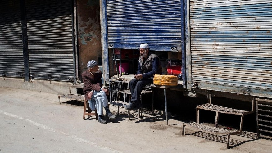 Kashmiri Muslim men sit outside a shop with shutters half closed during a strike in Srinagar, Indian controlled Kashmir, Saturday, April 11, 2015. Kashmiris closed shops and businesses in the disputed Himalayan region Saturday to protest India's plan to build townships for Hindus who fled a rebellion in Muslim-majority areas. Many of the Hindus, known as Pandits, had fled to Hindu-dominated areas in Jammu region or elsewhere in India in 1990. (AP Photo/Dar Yasin)