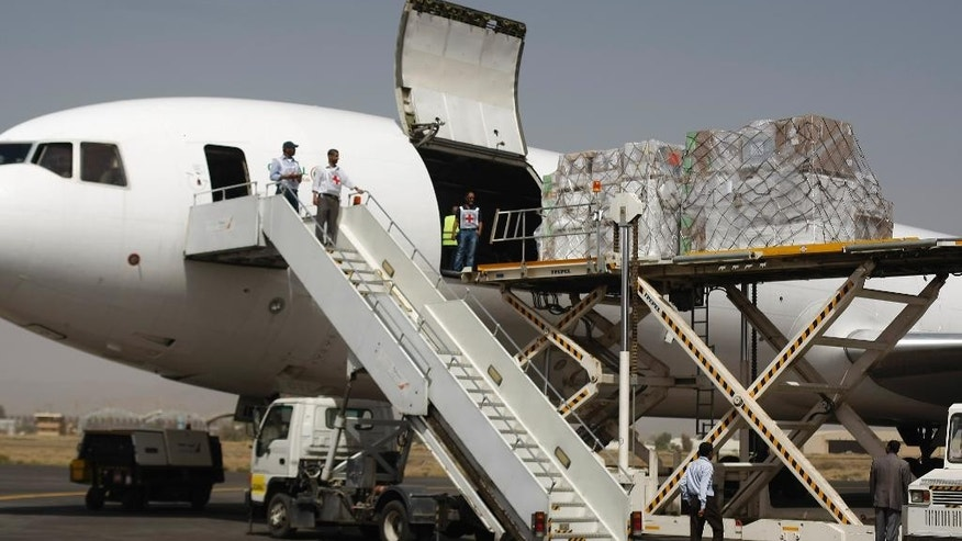 Aid workers unload a cargo plane with badly needed humanitarian relief supplies in Yemen's embattled capital following Saudi-led airstrikes that started more than two weeks ago, in Sanaa, Yemen, Saturday, April 11, 2015. (AP Photo/Hani Mohammed)