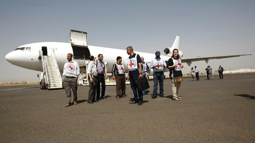 International Rescue Committee workers gather after they unloaded badly needed humanitarian relief supplies in Yemen's embattled capital following Saudi-led airstrikes that started more than two weeks ago, in Sanaa, Yemen, Saturday, April 11, 2015. (AP Photo/Hani Mohammed)