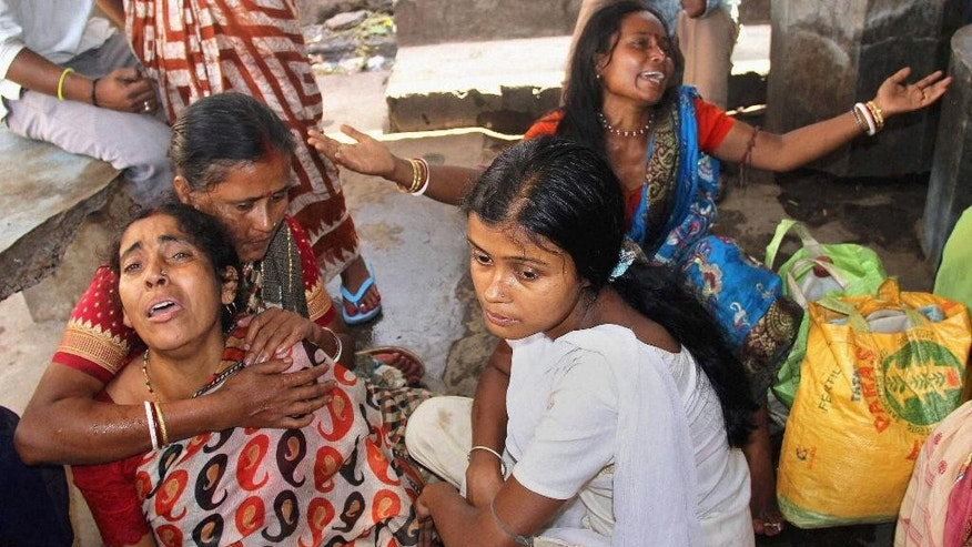 INDIA OUT - In this Friday, April 10, 2015 photo, relatives of victims of a bus accident weep at a hospital in Burdwan district in the eastern Indian state of West Bengal. Police were searching Saturday for the driver of an overcrowded bus that skidded into a ditch in eastern India, killing more than a dozen and leaving many more injured. The bus, which normally seats 54, had been so crowded with Hindu pilgrims that some were sitting on the roof, police said. (AP Photo/Press Trust of India)