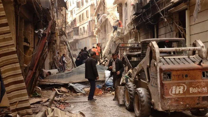 In this photo released by the Syrian official news agency SANA, Syrians gather between damaged buildings, in  the predominantly Christian and Armenian neighborhood of Suleimaniyeh, Aleppo, Syria, Saturday, April 11, 2015. Syrian state television and an activist group say opposition fighters have shelled the government-held neighborhood in the northern city of Aleppo, killing several people and wounding dozens. (AP Photo/SANA)