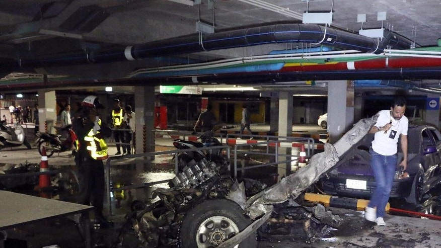 In this Friday, April 10, 2015 photo, Thai officers examine the wreckage of a pickup truck after an explosion at Samui Island in Surat Thani province, Thailand. The improvised bomb on Samui late Friday was hidden in the pickup truck and went off after a fashion show in the basement parking area of the Central Festival mall, the island's disaster prevention and mitigation chief Poonsak Sophonpathumrak told The Associated Press. (AP Photo/Daily News) THAILAND OUT