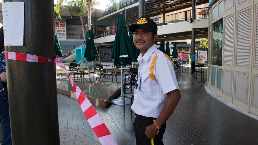 A security guard stands outside the closed Central Festival mall on Samui Island in Surat Thani province, Thailand, Saturday, April 11, 2015. An improvised bomb exploded on Samui late Friday that was hidden in a pickup truck and went off after a fashion show in the basement parking area of the Central Festival mall, the island's disaster prevention and mitigation chief Poonsak Sophonpathumrak told The Associated Press.  (AP Photo/Mark Baker)
