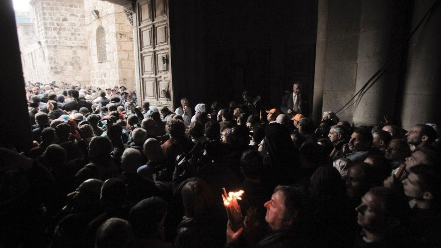 A Christian pilgrim holds up a candle as others gather at the church of the Holy Sepulcher, traditionally believed to be the burial site of Jesus Christ, during the ceremony of the Holy Fire in Jerusalem's Old City, Saturday, April 11, 2015. Thousands of Christians have gathered in Jerusalem for the ancient fire ceremony that celebrates Jesus' resurrection. (AP Photo/Dan Balilty)
