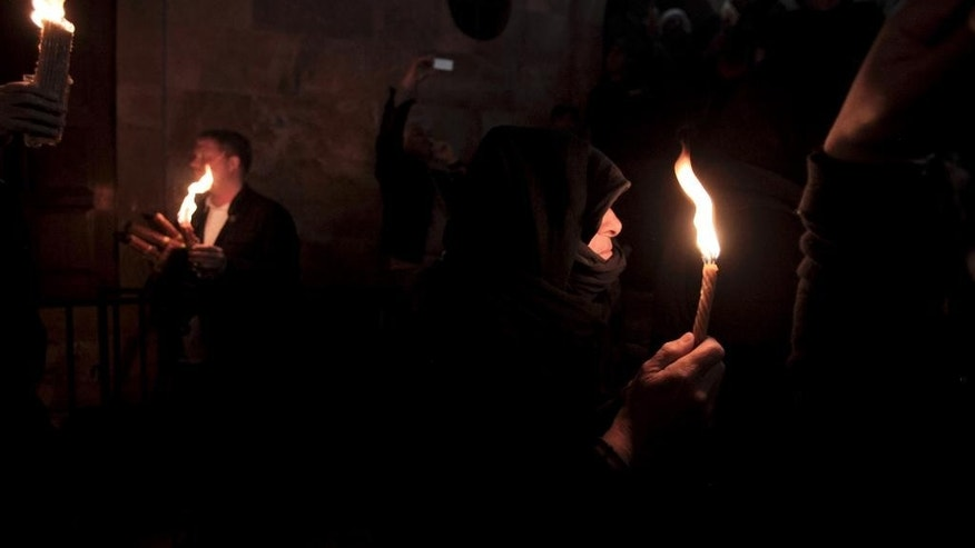 Christian pilgrims hold candles at the church of the Holy Sepulcher, traditionally believed to be the burial site of Jesus Christ, during the ceremony of the Holy Fire in Jerusalem's Old City, Saturday, April 11, 2015. Thousands of Christians have gathered in Jerusalem for the ancient fire ceremony that celebrates Jesus' resurrection. (AP Photo/Dan Balilty)