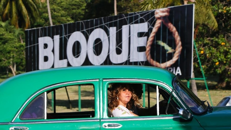 "A woman commutes in a private collective taxi passed a sign reading ""Blockade, the longest genocide in history,"" in reference to the U.S. trade embargo imposed on Cuba,  in Havana, Cuba, Friday, April 10, 2015. President Barack Obama signaled Thursday he will soon remove Cuba from the U.S. list of state sponsors of terrorism, boosting hopes for improved ties as he prepared for a historic encounter with Cuban President Raul Castro during the Summit of the Americas taking place in Panama. (AP Photo/Desmond Boylan)"