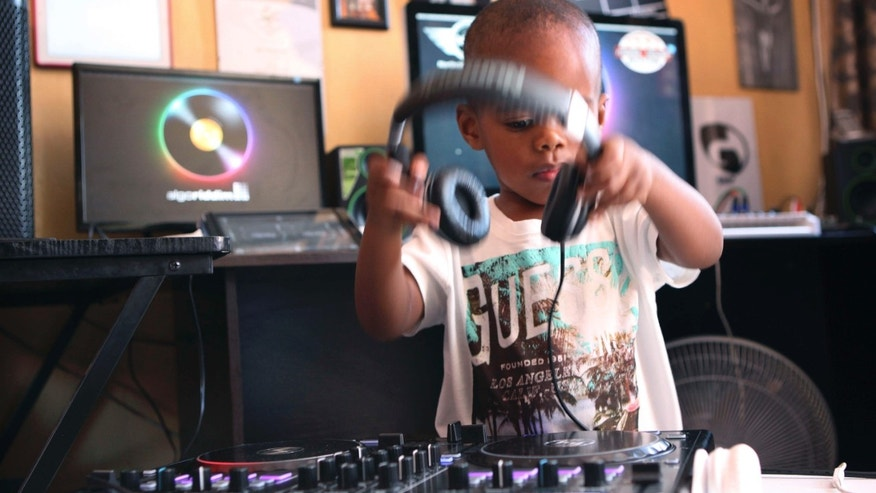 April 6, 2015: Two-year-old Oratilwe Hlongwane, also known as DJ AJ to his fans, removes his headphones after playing with the buttons and knobs of a sophisticated music system in control of the beat of the bass-heavy house music at his Alexandra home in Johannesburg.