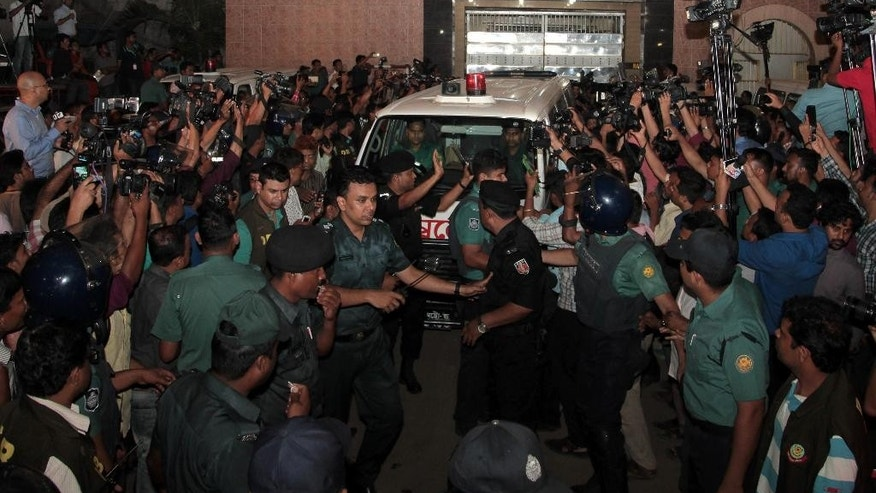 Bangladeshi security personnel cordon an ambulance leaving Central Jail carrying the body of Mohammad Qamaruzzaman, an assistant secretary general of Jamaat-e-Islami party, after he was executed in Dhaka, Bangladesh, Saturday, April 11, 2015. Authorities in Bangladesh on Saturday executed the senior Islamist party official convicted of crimes against humanity during the country's 1971 independence war against Pakistan, two officials and TV stations said. (AP Photo/ A.M. Ahad)