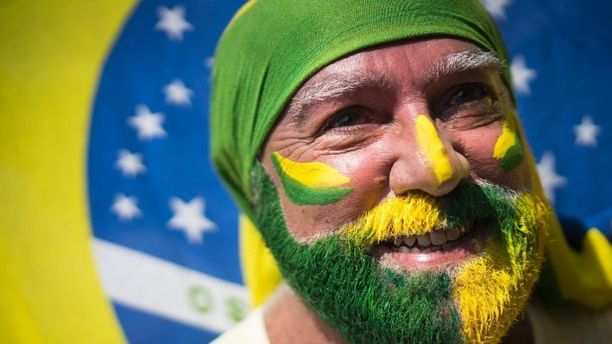 A protester with his face painted holds a flag during a protest at Copacabana beach in Rio de Janeiro, Sunday, April 12, 2015. Anti-government demonstrators began streaming into the streets of cities throughout Brazil on Sunday to demand the impeachment of President Dilma Rousseff. (AP Photo/Felipe Dana)