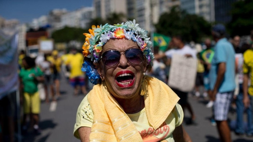A demonstrator shows Brazilian coins, that she says are worthless, during an anti-government protest at Copacabana beach, in Rio de Janeiro, Brazil, Sunday, April 12, 2015. Anti-government demonstrators marched in cities throughout Brazil to demand the impeachment of President Dilma Rousseff. In Rio de Janeiro, a protest along the golden sands of Copacabana drew several hundred people, a far cry from the several thousand-strong turnout last month. (AP Photo/Silvia Izquierdo)