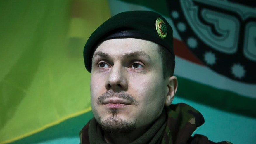 In this photo taken on Monday March 2, 2015, Adam Osmayev, the commander of a battalion of Chechens fighting against Russia-backed rebels, is in the town of Lysychansk, Ukraine. Russian pro-Kremlin newspapers published reports based on unidentified sources in the security services that accused the Ukrainian government and Osmayev of ordering the murder of Russian opposition leader Boris Nemtsov, the claims Osmayev has denied. (AP Photo/Olya Engalycheva)