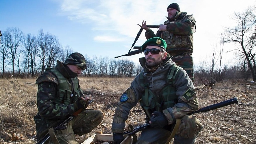 In this photo taken on Wednesday, Feb. 25, 2015, fighters of a Chechen battalion fighting against Russia-backed rebels, reload in the town of Lysychansk, Ukraine. Russian pro-Kremlin newspapers published reports based on unidentified sources in the security services that accused the Ukrainian government and Osmayev of ordering the murder of Russian opposition leader Boris Nemtsov, the claims Osmayev has denied. (AP Photo/Olya Engalycheva)
