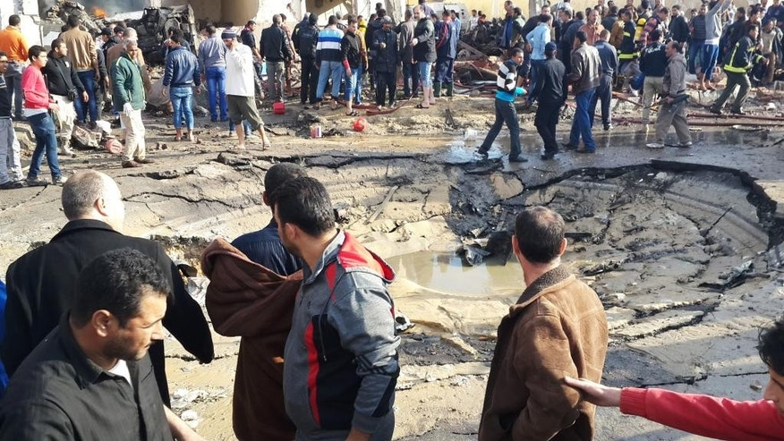 Egyptians gather around the crater following a bombing that struck a main police station in the capital of the northern Sinai province in el-Arish, Egypt, Sunday, April 11, 2015. The explosion comes hours after a roadside bomb killed six soldiers traveling south of el-Arish in an armored vehicle. The region has been hit by an Islamic insurgency by a group that recently pledged allegiance to the Islamic State. (AP Photo/Muhamed Sabry)