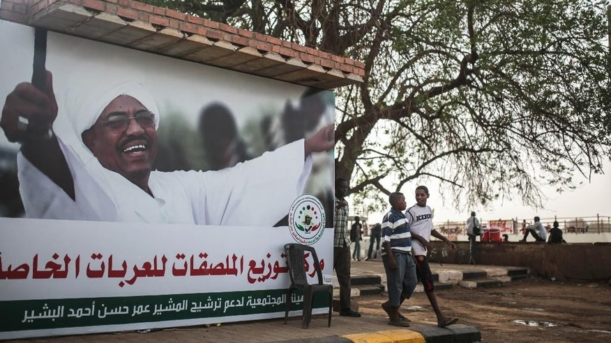 "In this Saturday, April 11, 2015 photo, Sudanese boys walk past an election campaign banner in support of President Omar al-Bashir, in Khartoum, Sudan, that reads ""community commission in support of nominating Marshal Omar al-Bashir."" Nearly 13 million people are registered to vote for president and the 450-member legislative council starting Monday. Some 11,000 polling centers will be open through Wednesday, and results are expected on April 27.(AP Photo/Mosa'ab Elshamy)"
