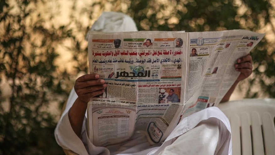 In this Saturday, April 11, 2015 photo, a man reads a newspaper during a sit-in organized by Sudanese opposition parties at the headquarters of Umma, one of Sudan's biggest opposition parties, in Khartoum, Sudan, to denounce the upcoming presidential elections where longtime autocratic President Omar al-Bashir is expected to secure easy victory. (AP Photo/Mosa'ab Elshamy)