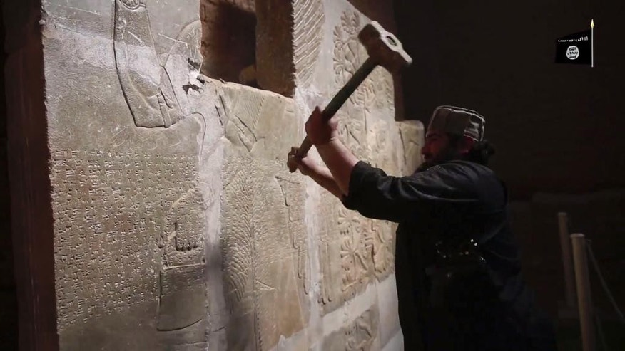 "In this image made from video posted on a militant social media account affiliated with the Islamic State group late Saturday, April 11, 2015, purports to show a militant taking a sledgehammer to an Assyrian relief at the site of the ancient Assyrian city of Nimrud, which dates back to the 13th century B.C., near the militant-held city of Mosul, Iraq. The destruction at Nimrud, follows other attacks on antiquity carried out by the group now holding a third of Iraq and neighboring Syria in its self-declared caliphate. The attacks have horrified archaeologists and U.N. Secretary-General Ban Ki-moon, who last month called the destruction at Nimrud ""a war crime.""(militant video via AP)"