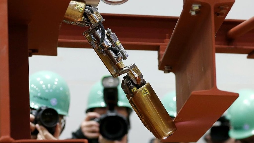 FILE - In this Thursday, Feb. 5, 2015 file photo, a remote-controlled robot that looks like an enlarged fiberscope crawls down into the mock-up of a primary containment chamber of Fukushima Dai-ichi nuclear plant, during a demonstration for the media at a government facility in Hitachi, Ibaraki Prefecture, northeast of Tokyo. Tokyo Electric Power Co., the operator of the wrecked Fukushima nuclear plant, said Monday, April 13, the first robot, the same type shown in the photo, sent inside one of melted reactors stalled before finishing its work but it collected data that indicates a path to send robots deeper into the reactor is intact. TEPCO said the robot stalled after completing two-thirds of Friday's planned mission inside the Unit 1 containment vessel. (AP Photo/Shizuo Kambayashi)