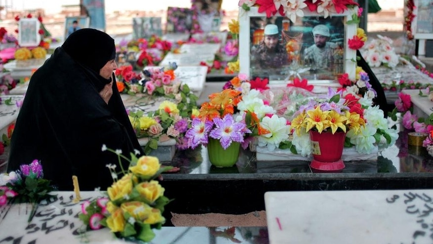 In this Saturday, April 11, 2015, photo, a woman visits her son's grave at a cemetery for militiamen killed from fighting with Islamic State group militants in Najaf, Iraq. Every chapter of Iraq's modern history can be seen in this great, sprawling city of the dead, its mausoleums stretching across the horizon from one of Shiite Islam's holiest shrines. And now, its sandy expanse grows again yet with the war dead killed by the country's latest adversary, the extremists of the Islamic State group. (AP Photo/Jaber al-Helo)