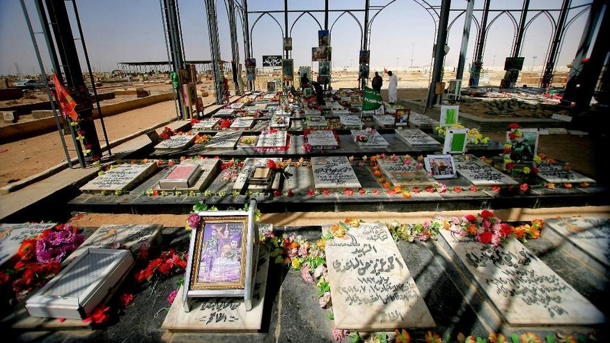 In Saturday, April 11, 2015 photo, people visit a cemetery for militiamen killed from fighting with Islamic State group militants in Najaf, Iraq. Every chapter of Iraq's modern history can be seen in this great, sprawling city of the dead, its mausoleums stretching across the horizon from one of Shiite Islam's holiest shrines. And now, its sandy expanse grows again yet with the war dead killed by the country's latest adversary, the extremists of the Islamic State group. (AP Photo/Jaber al-Helo)