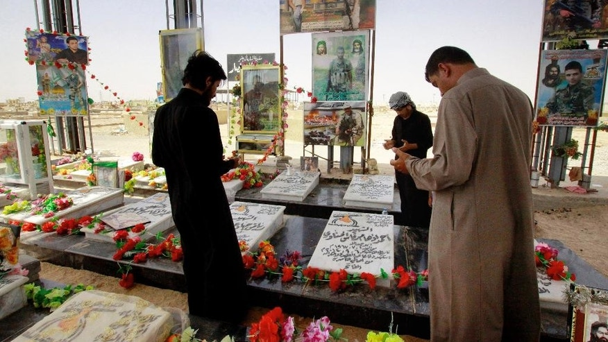In Saturday, April 11, 2015 photo, men pray at a cemetery for militiamen killed from fighting with Islamic State group militants in Najaf, Iraq. Every chapter of Iraq's modern history can be seen in this great, sprawling city of the dead, its mausoleums stretching across the horizon from one of Shiite Islam's holiest shrines. And now, its sandy expanse grows again yet with the war dead killed by the country's latest adversary, the extremists of the Islamic State group. (AP Photo/Jaber al-Helo)