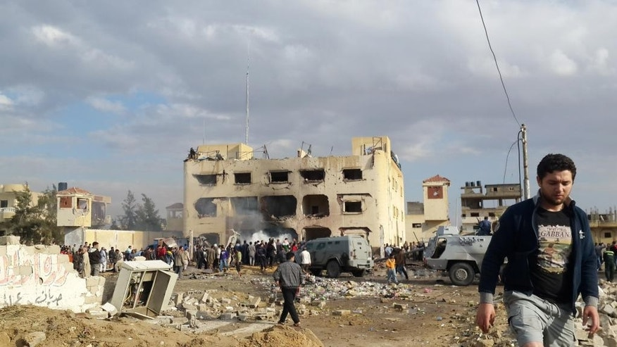 In this Sunday, April 12, 2015 photo, Egyptians gather at the scene following a bombing that struck a main police station in the capital of the northern Sinai province in el-Arish, Egypt. The explosion came hours after a roadside bomb killed many soldiers traveling south of el-Arish in an armored vehicle. The region has been hit by an Islamic insurgency by a group that recently pledged allegiance to the Islamic State. (AP Photo/Muhamed Sabry)