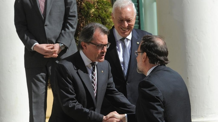 Spanish Prime Minister Mariano Rajoy, right, shakes hands with President of Catalan regional government Artur Mas before the informal ministerial meeting in Barcelona, Spain, Monday April 13, 2015. Foreign ministers from European and North African countries have gathered in Barcelona to discuss ways to fight terrorism and illegal immigration. Europe has been hit by increasing waves of migration from Syrians and sub-Saharan Africans crossing the Mediterranean in flimsy boats in a bid to get to Europe. (AP Photo/Manu Fernandez)
